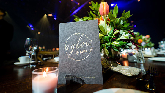 image of table with program and flowers from a night aglow ahn 2019 gala event