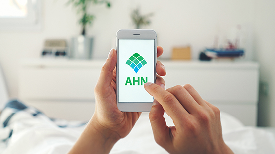 image of hands holding a phone displaying AHN's website