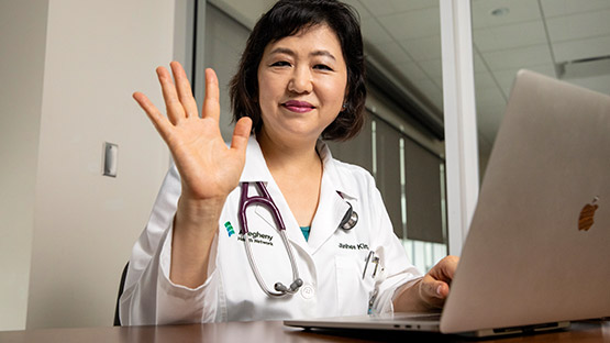 Image of doctor waving while on computer