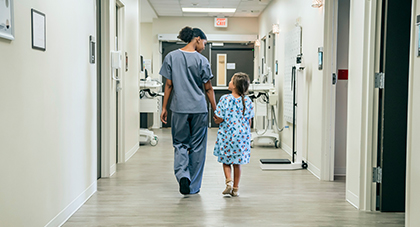 image of a nurse walking with a little girl down a hospital hallway