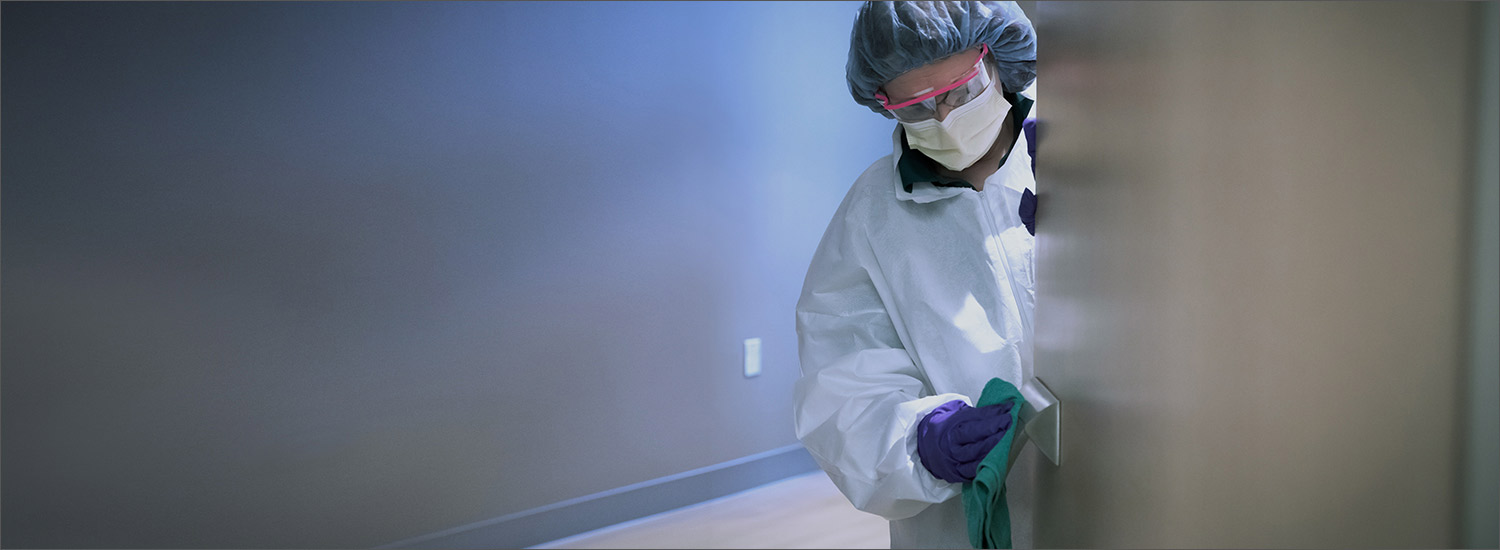 Image of a person sanitizing a door at an AHN hospital