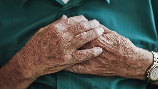 image of an elderly man's hands resting on his chest