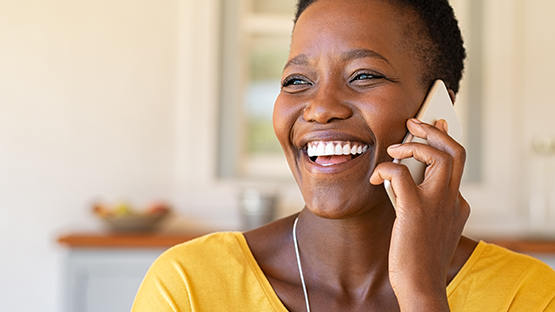black woman smiling while she places a call on her cell phone