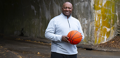 AFIB survivor smiling holding a basketball