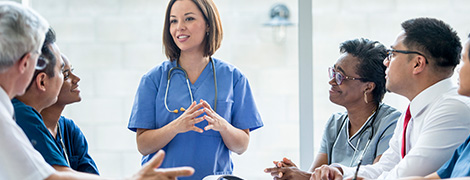 image of a doctor speaking to a group of her colleagues