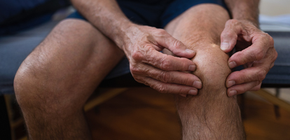 image of a man holding his knee