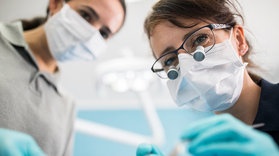 image of a dentist and dental assistant from the view of the patient