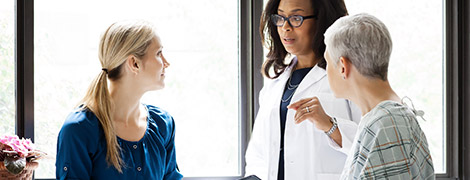 image of a doctor talking to a patient and her colleague