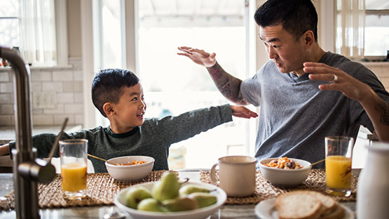image of a father and son playing during breakfast