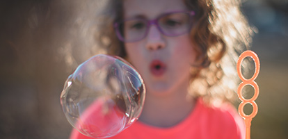 image of a woman blowing bubbles