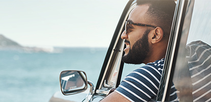 Man wearing sunglasses smiling as he views the beach from his car window