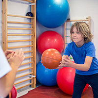 image of young boy throwing a medicine ball during physical therapy appointment