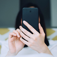 image of a woman laying in bed making a same day appointment on her phone