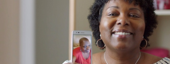 image of a cancer survivor showing a photo of herself during treatment